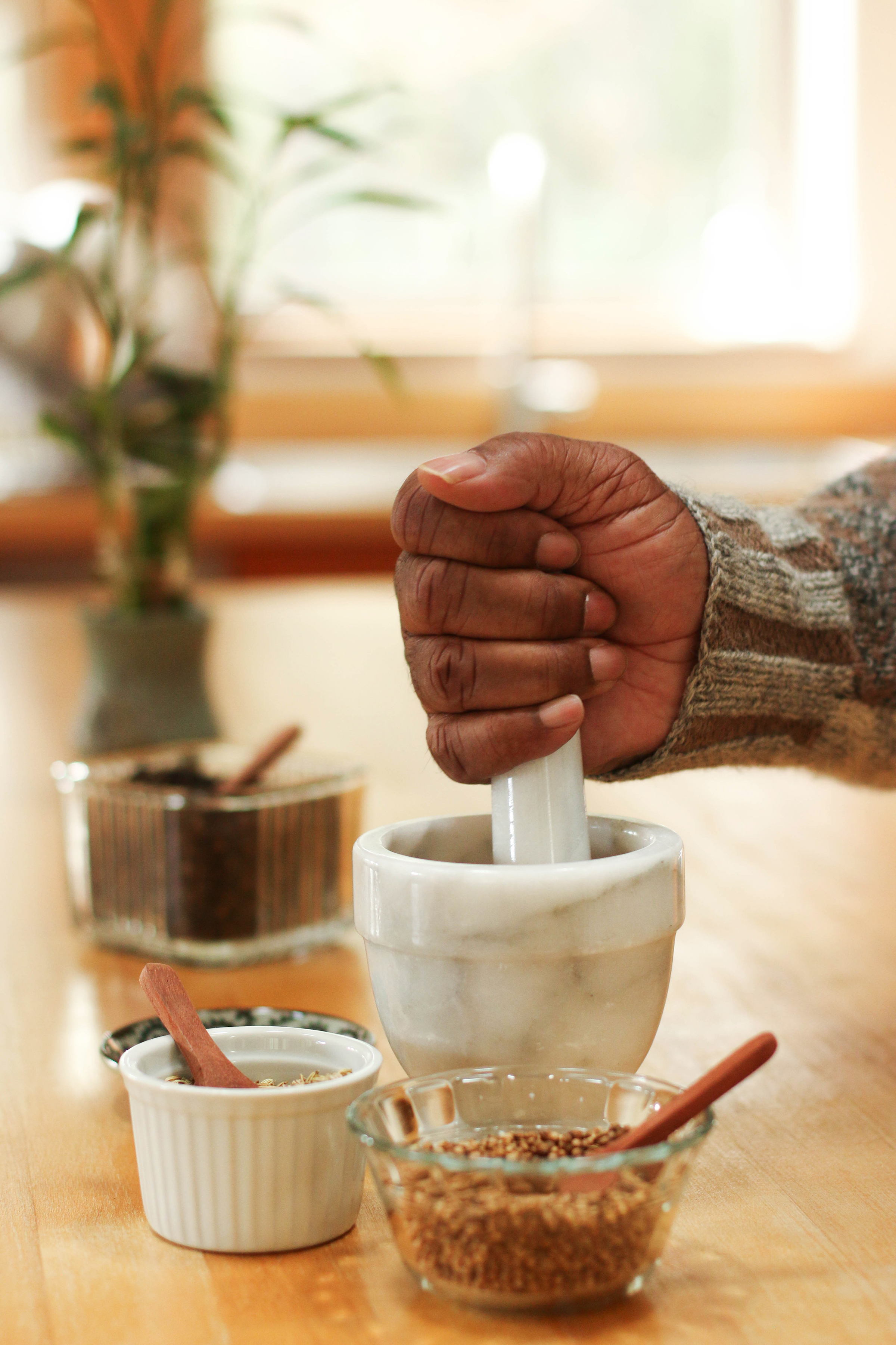 hand-crushing-spices-with-white-marble-mortar-and-pestle-surrounded-by-bowls-of-whole-spices