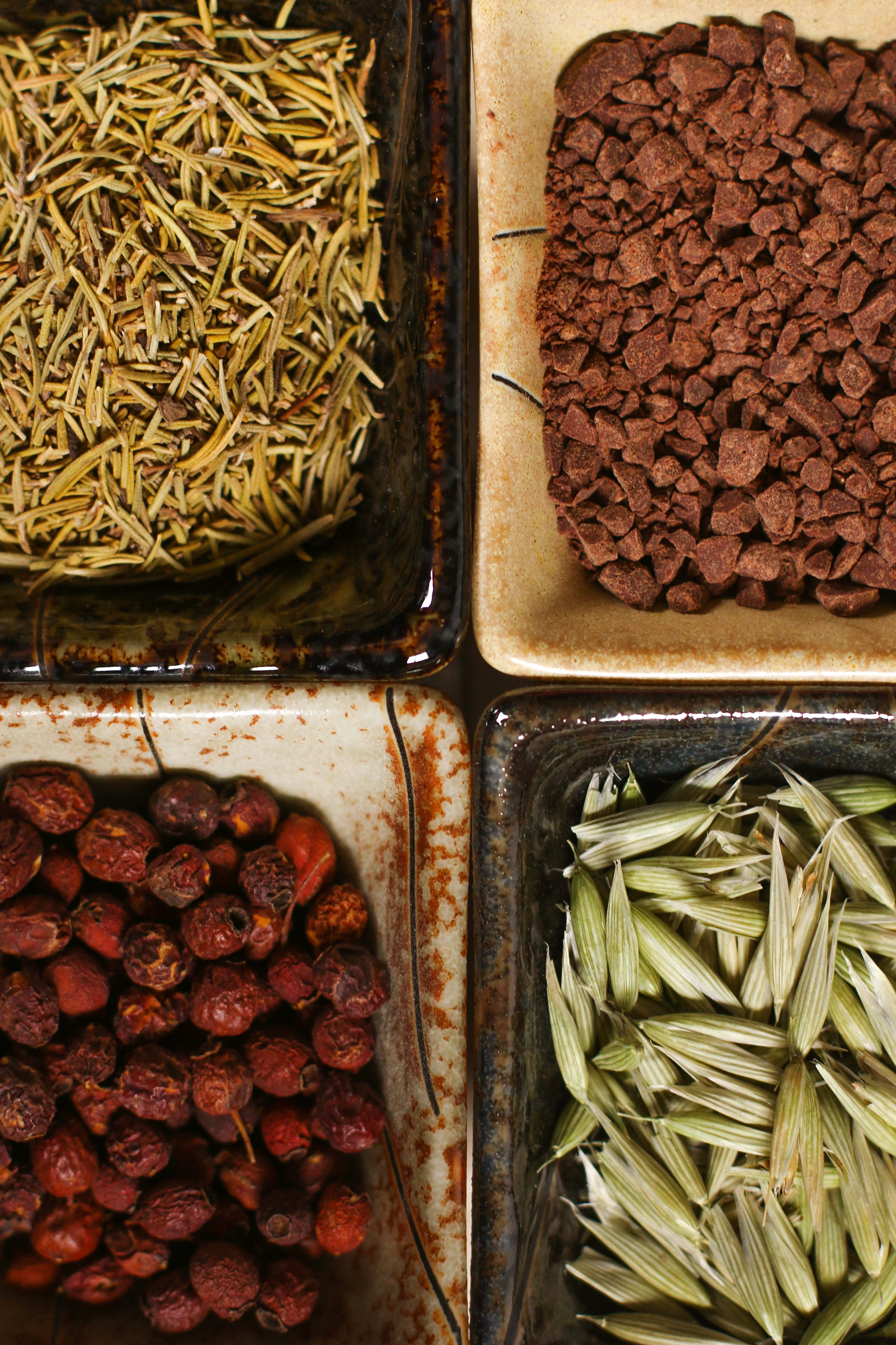 square-dishes-of-dried-herbs-for-heart-health-with-hawthorn-berries-cacao-oat-tops-and-rosemary